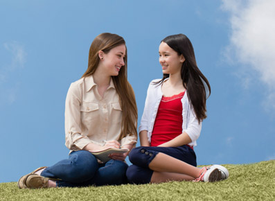 Two Girls Sitting on Grassy Hill